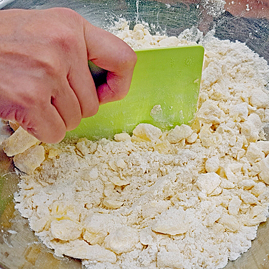 Zutaten des Mürbteigs mit einer Teigspachtel zerbröseln