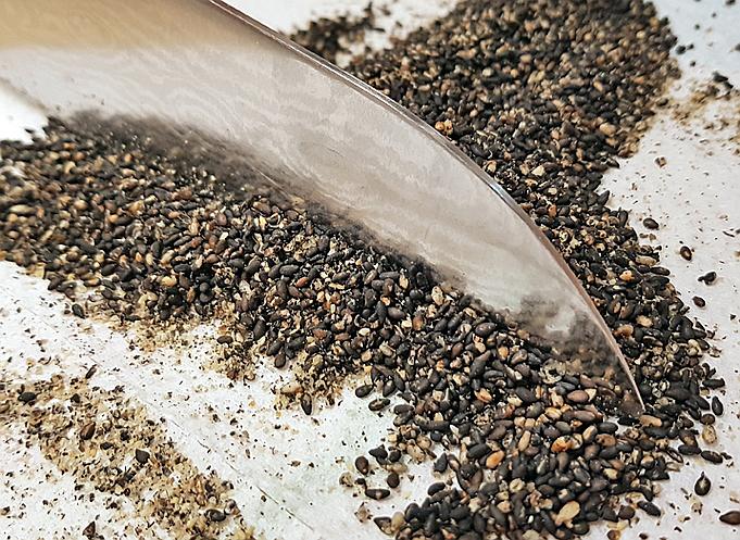 Schwarzen Sesam auf einem Küchentuch hacken