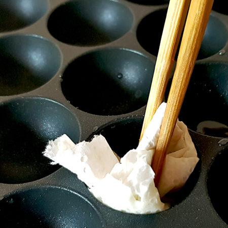 Takoyaki-Grill mit Küchenpapier und Stäbchen einölen