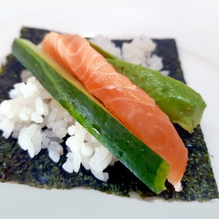 Noriblatt mit Reis Avokado Gurke und Lachs belegen