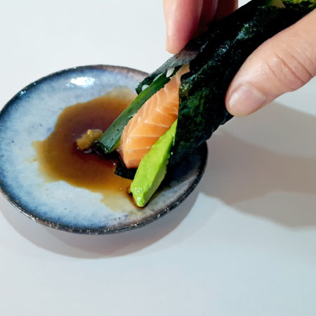 Temakisushi in den Wasabi-Shoyu-Dip tauchen