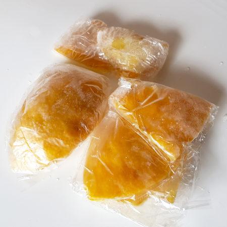 Gefrorene Yuzu-Hautstücke portionsweise in Folie eingewickelt