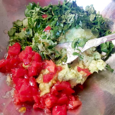 Zutaten der Guacamole mischen